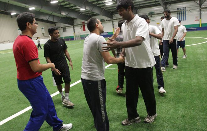 An indoor cricket league started this year.  There are four teams whose players are primarily from the India and surrounding countries, who are now working in Buffalo or going to school at UB.  They played their games at the Epic Center in Lancaster, Thursday, Feb. 27, 2014. The Bulldozers and the Strikers shake hands after the Bulldozers' win.
