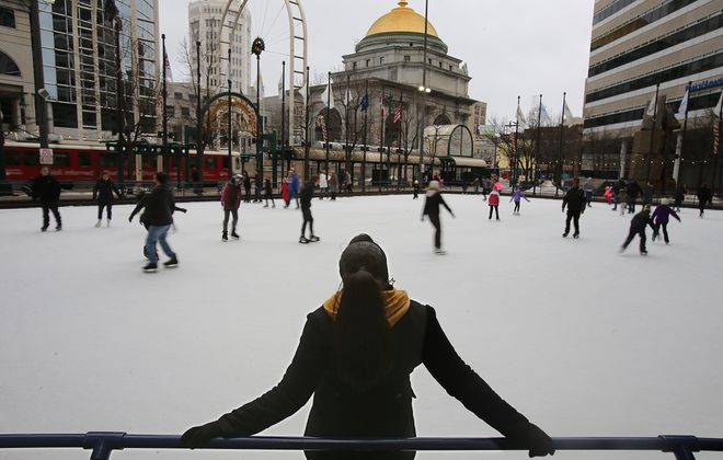 A skater takes in the scenery at Rotary Rink in downtown Buffalo. As housing development quickens, more people are returning to the city from the suburbs.