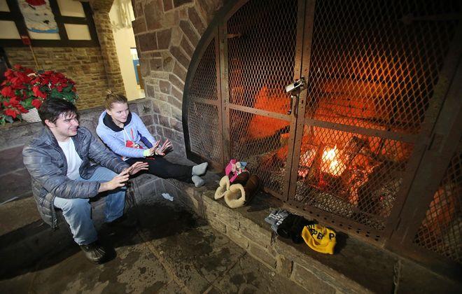 Vadim Fedoriskin of Orchard Park, left, and Galina Zheliazniuk of Amherst stay warm by the fireplace at Chestnut Ridge Casino. (Robert Kirkham/Buffalo News)
