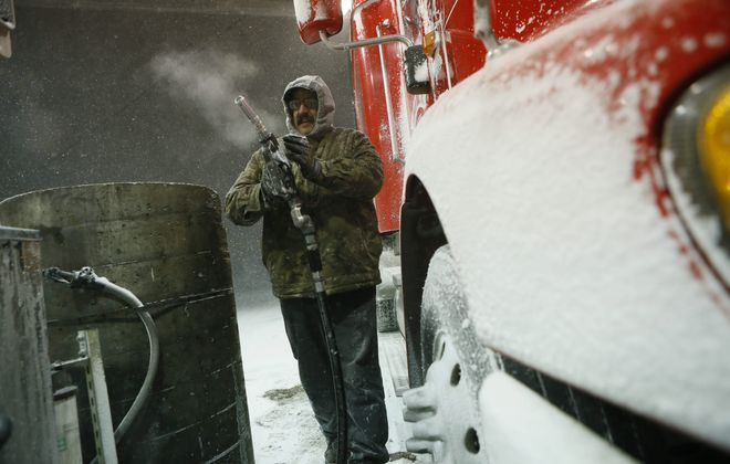 Steve DeMarco of Sandusky, Ohio, fills up his tank with diesel Monday before settling down for the night at Jim's Truck Stop on Walden Avenue in Cheektowaga. Monday's storm led to the Thruway's closure.