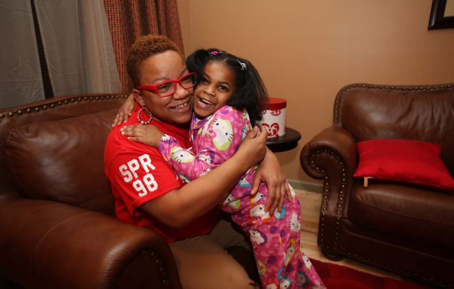 Orniece Hill hugs her daughter, Milan, 5, after her school bus was delayed for several hours by Monday's blizzard. After being trapped in weather-snarled traffic, the bus dropped Milan off at 7:25 p.m.