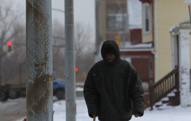 Darnell Johnson shovels his sidewalk at the corner of Swan and Spring in Buffalo on Tuesday.
