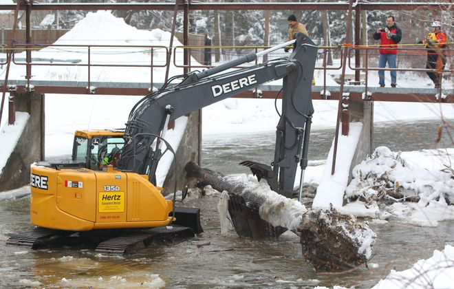 A crew removes debris in Ellicott Creek near an overpass in Williamsville on Friday. Keeping the water flowing  is key.
