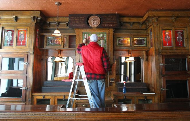 Sal Buscaglia works on cleaning an antique bar in Ulrich's 1868 Tavern, which will host a re-opening party. (Mark Mulville/Buffalo News)