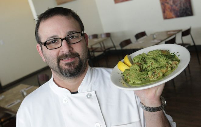 The secret's in the sauce as owner and chef Oded Rauvenpoor presents a plate of the green wings at the Falafel Bar on Sheridan Drive in Amherst.