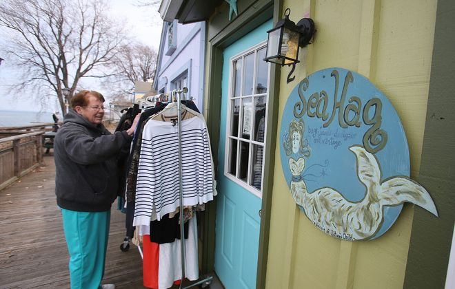 """Scotty Johnson arranges clothing outside The Sea Hag, a business she owns, as the Lakeview Village Shoppes in Olcott get ready for Saturday's opening of a season in which, the town liaison says, """"there's something going on here"""" every weekend."""