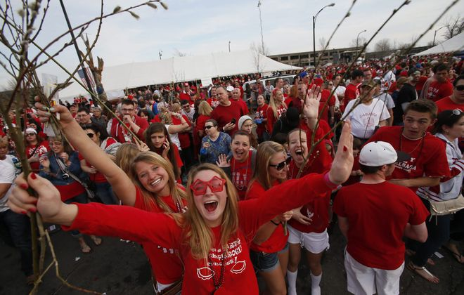 Enthusiastic revelers, decked out in red and  holding pussy willows, cheer during the Dyngus Day Parade in Polonia on Monday.