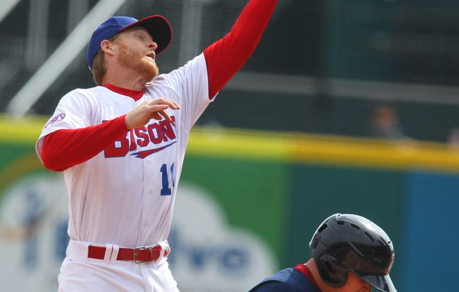 Bisons' Dan Johnson makes a catch over Pawtucket's Christian Vasquez on Sunday.