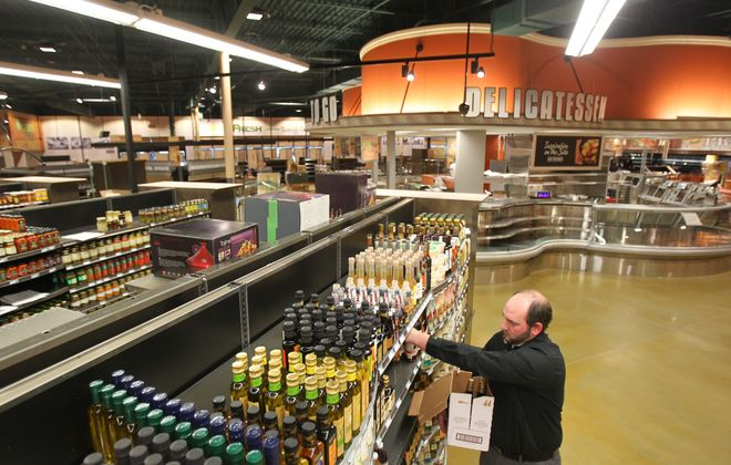 Orchard Fresh guest services team leader Jon Neunder stocks shelves at the Orchard Park store on March 28, 2013.
