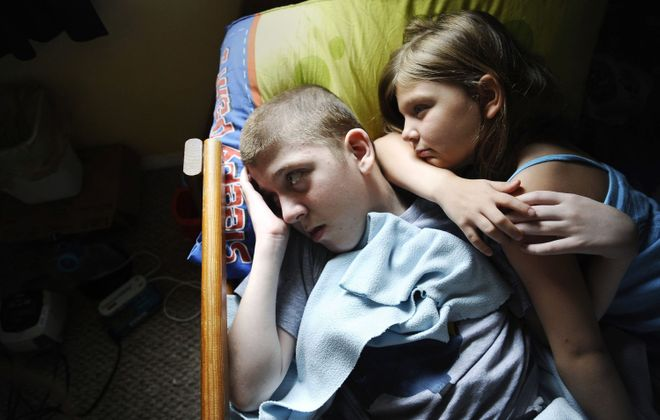"""William """"Mick"""" Smith, 12, left, lies in bed with his sister Martie Smith, 7, as Mick is fed by a gastric feeding tube while they watch TV. Mick has an undiagnosed progressive neuromuscular disease."""