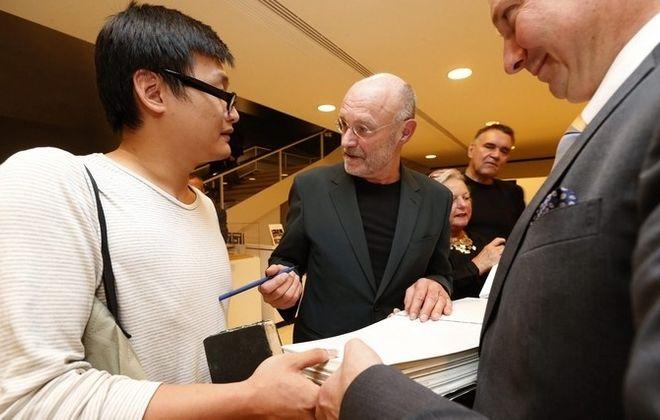 Albright-Knox Art Gallery director Janne Sirén, right, holds a book as Anselm Kiefer, center, autographs it for Shen Linghao. (Robert Kirkham/Buffalo News)