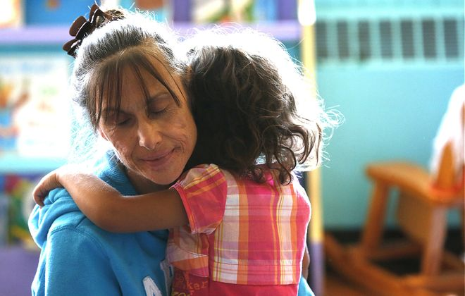 Pre-K teacher Sue Rogacki offers a human touch to an upset child at Our Lady of Hope School at St. Luke's Mission of Mercy on Walden Avenue in Buffalo on Wednesday.
