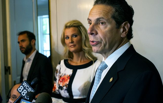 Governor Andrew Cuomo, stands with his partner Sandra Lee, center, while addressing members of the media after casting a vote in the primary election Tuesday, Sept. 9, 2014, at the Presbyterian Church of Mount Kisco in Mount Kisco, N.Y. (AP Photo/Craig Ruttle)