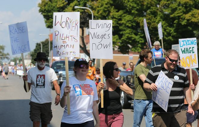 Labor supporters carry signs during the annual Labor Day parade along Abbott Road in Buffalo on Monday.
