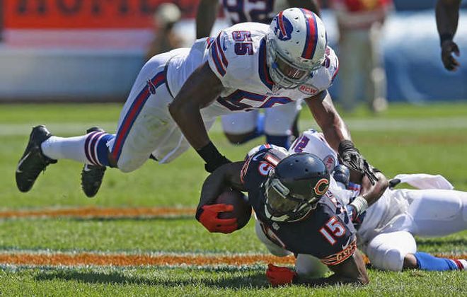 Brandon Marshall is tackled by the Bills' Leodis McKelvin and Jerry Hughes. (Getty Images)