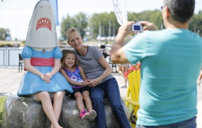 "Diane Garey of Boston and her granddaughter Keria Bieler, 5, pose at Canalside with the ""Shark Girl"" statue by artist Casey Riordan Millard. (Derek Gee/Buffalo News file photo)"