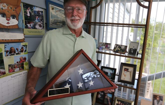 Charlie Foster, a com- bat Marine in Korea, displays an encased U.S. flag given to him by grandson Matthew Foster, a Navy veteran.