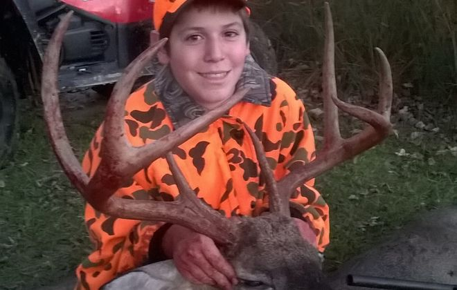 Braden Colby with his big 8-point buck taken on a hunt with his dad, Scott Colby.