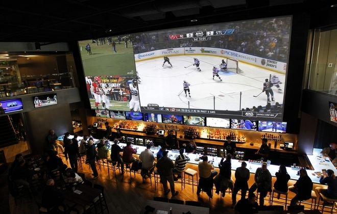 Patrons of (716) Food and Sport watch a hockey game on a 38-foot TV screen that is also visible from the second-floor balcony. The new 13,000-square-foot sports bar and restaurant at HarborCenter officially opened at 3 p.m. Friday. (Sharon Cantillon/Buffalo News)
