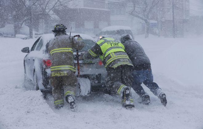 Firefighters from West End Hose Company in Depew help a stuck motorist on Transit Road near George Urban Boulevard, Tuesday.  (Derek Gee/Buffalo News)