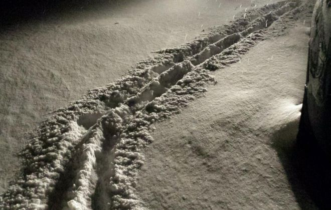 A few inches of snow covers the ground in Elma late Monday night, with the pileup likely due to winds.