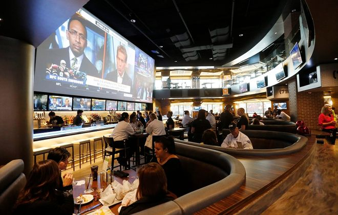 A look at the dining area of (716) Food and Sport, dwarfed by the massive television. (Derek Gee / Buffalo News)