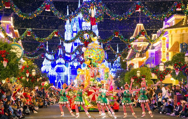 """Snowflakes gently fall on fans and floats at """"Mickey's Christmas Parade"""" in the Magic Kingdom."""