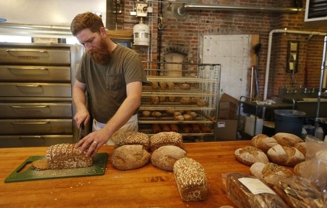 Above left, Kevin Gardner slices fresh bread at Five Points Bakery on Brayton Street on Tuesday. Above right, Melissa Gardner puts a plate of sticky buns on the counter of the newly reopened bakery. (Photos by Derek Gee/Buffalo News)