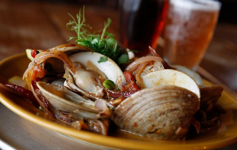 Littleneck clams in a white-win butter broth with roasted red peppers and peas from Black Iron Bystro, joining the Local Restaurant Week lineup this spring. (Sharon Cantillon/Buffalo News)