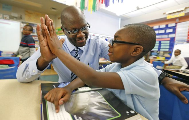 Principal Gregory Mott encourages second-grader Joseph Allums to keep up his good reading skills.