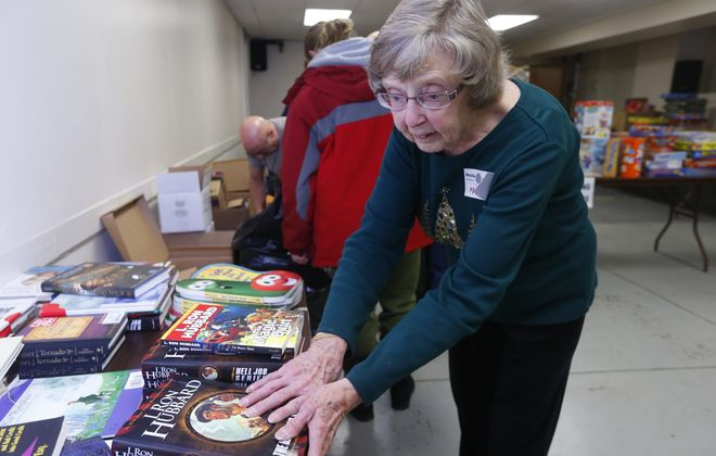 Mickey Sprague arranges some of the toys to be distributed to a  distributes toys and books with the help of Jack Walsh ,17, a Junior from Canisius High School at Response to Love Center,  in Buffalo, N.Y. , on Thursday  December  18, 2014. Sprague  helps out  out with the toy distribution at Response to Love, and puts a lot of thought into the process so the child receives the right gift. (John Hickey/Buffalo News)