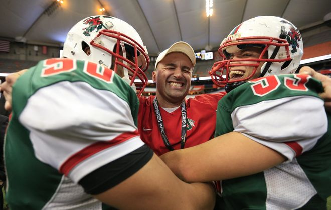 Jamestown coach Tom Langworthy embraces Jacis Blake, left, and Damien Jackson at the Carrier Dome.