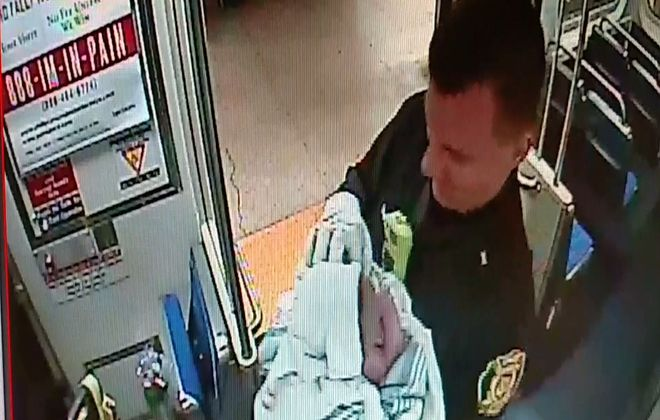 In this image provided by the subway authority, Philadelphia transit police Sgt. Daniel Caban holds a baby boy he helped deliver aboard a train.