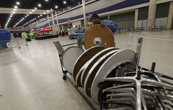 Dennis Robinson sets up tables for the First Night celebration on the second floor of the Buffalo Niagara Convention Center on Tuesday. (Robert Kirkham/Buffalo News)