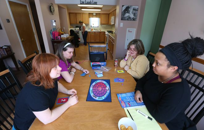 Senior residential supervisor Fatima Johnson, right, plays a game with, from left, Dana Kominiarek, Amy Hartman and Sarah Doueck at their group home in Amherst last month.