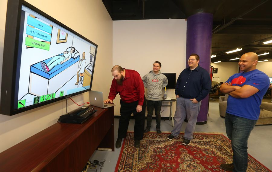 "Bill Stewart, left, types into his laptop as Eric Keller, center, and Dan Griggs  watches. Stewart and Griggs ""Queen City Careers"" is the front-runner in Buffalo's computer game competition."