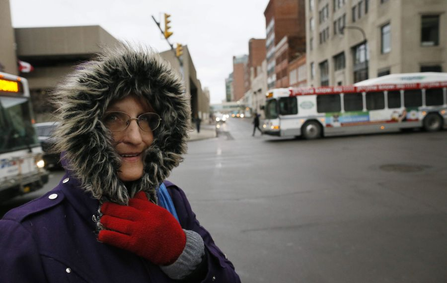Debbie Kelley braces herself from the wind as she walks down Court Street on her way to work, Monday morning, March 30, 2015.  (Derek Gee/Buffalo News)