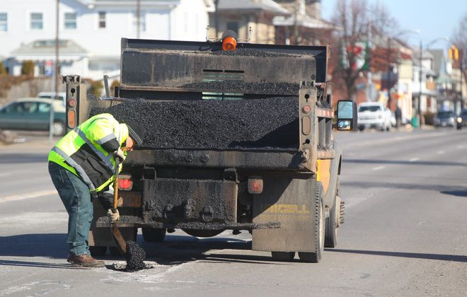 Don Allen Jr. fills potholes on Delaware Avenue near Hertel in Buffalo on Sunday, when the city had four crews out working.