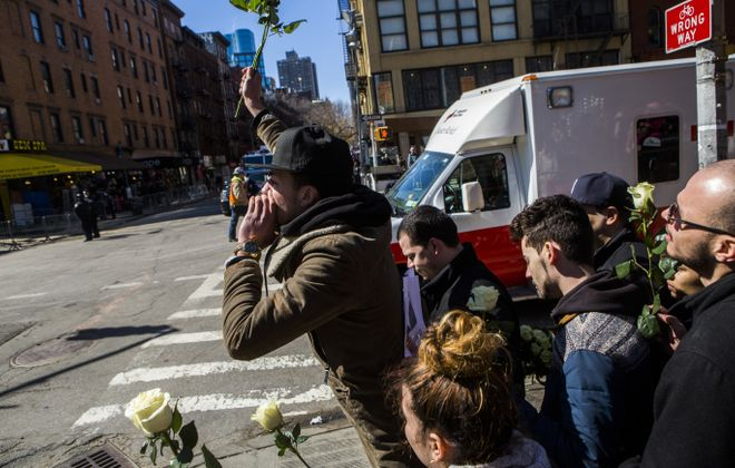 Neal Figueroa, whose brother, Nicholas, was missing after Thursday's blast, throws roses towards the site after the first of two bodies was recovered Sunday.