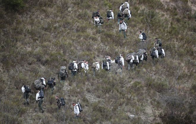 French military personnel walk up the mountainside Wednesday near Seyne, France, near where wreckage is believed to be.