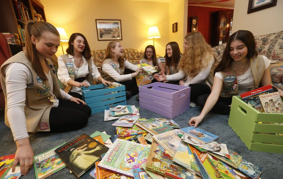 Girl Scouts from Troop 31749 sort books into freshly painted wooden totes. From left are Taylor Sniatecki, Della Knapp, Annabeth Collis, Emma Dileas, Jenna Sniatecki, Grace DeRoo and Hailey Cullen. The books were donated to Gerard Place.
