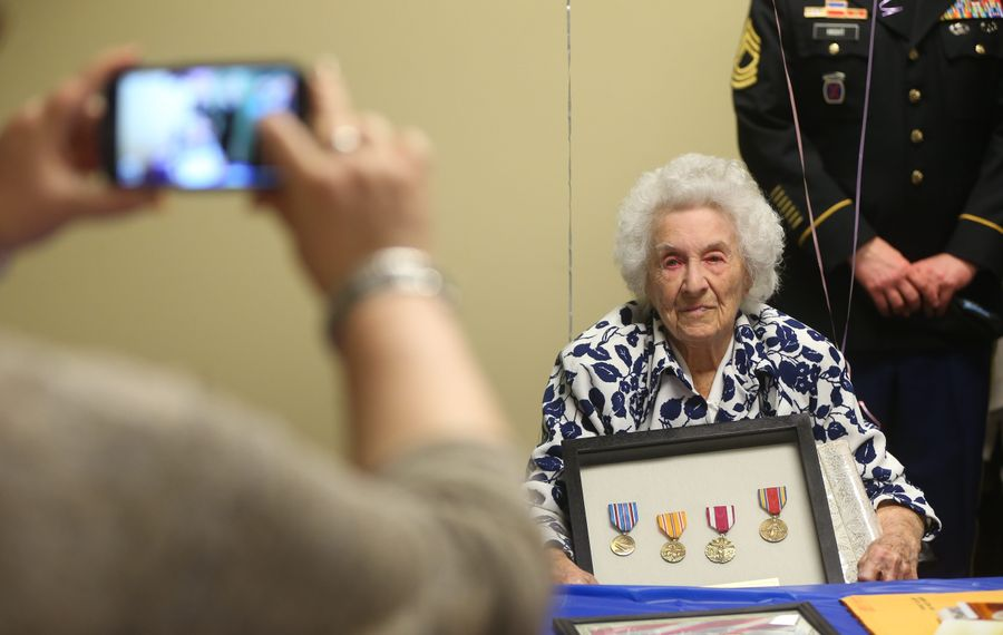 """Phyllis """"Jo"""" Thompson shows medals at party in Father Baker Manor."""