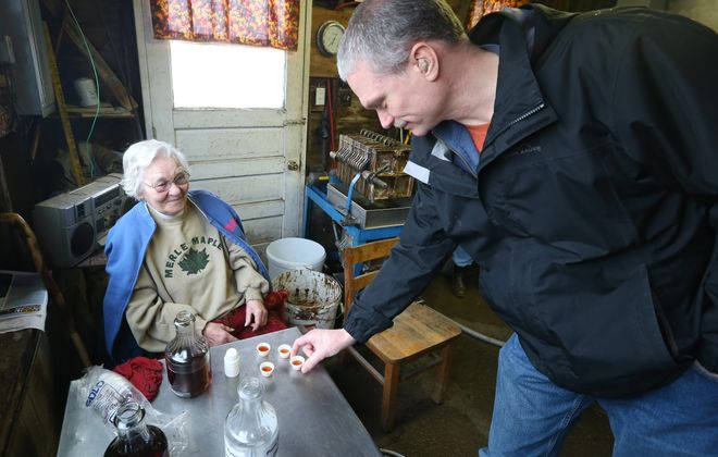 100-year-old Florence Merle passes out maple syrup samples for people touring the Merle Maple Farm in Attica on Saturday.  maple products line the shelves at Merle Maple Farm; and the sun shines through a row of maple syrup bottles, casting a golden glow.