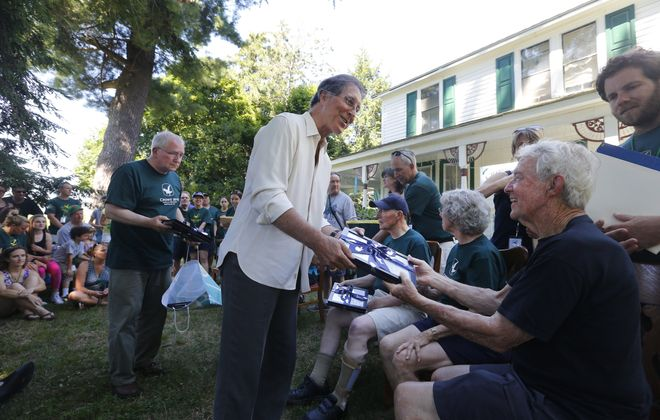 Former Buffalo Bill and Notre Dame alum Ed Rutkowski presents gifts to John Crowe, Ann Cook and Jim Crowe in Eden on Thursday.
