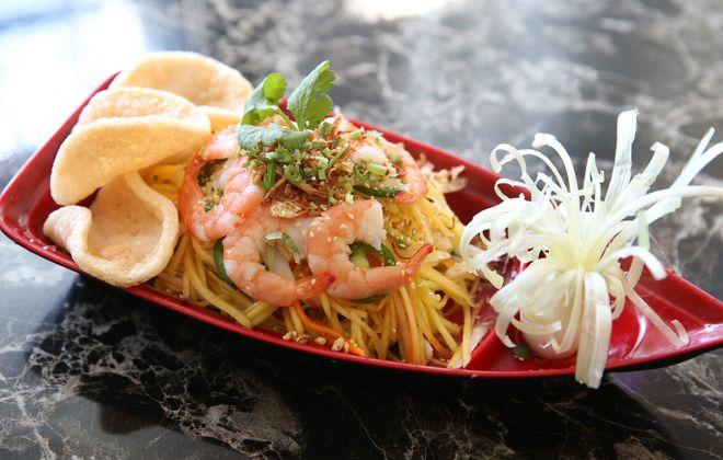 Vietnamese Mango Salad is made with pickled daikon and carrots, fresh mango, lotus rootlet, onion, herbs, shrimp and crackers.  (Sharon Cantillon/Buffalo News)