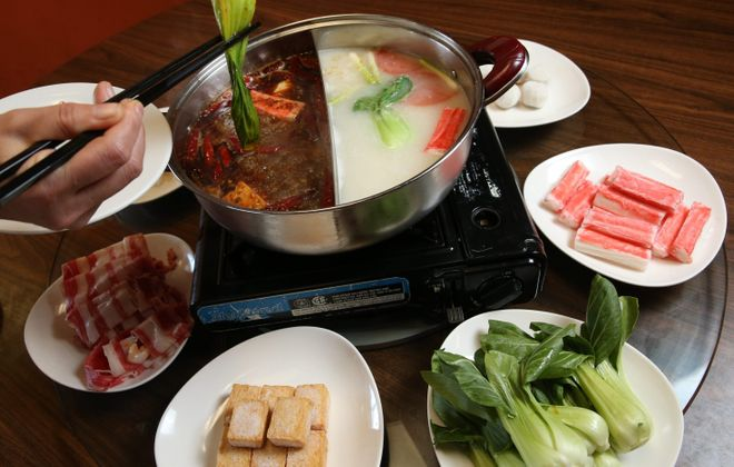 The Chong Qing hot pot at China Star, 4001 Sheridan Drive, Amherst, is served family style. Diners cook their dinners in the simmering broths, spicy Sichuan or mild chicken scallion. (Sharon Cantillon/Buffalo News)