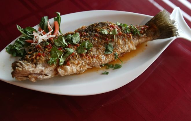 Either sea bass or red tilapia deep-fried whole and topped with green pepper, onion and pineapple in the chef's special lightly sour sauce. (Sharon Cantillon/Buffalo News)