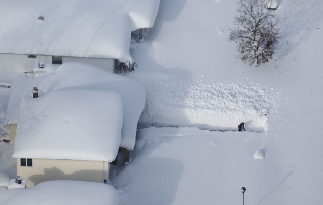 This dramatic photo showing Christopher Robinson digging out in Depew on Nov. 19, 2014, went viral during the storm.