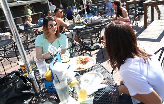 The Ebenezer Ale Huse at 4348 Seneca St. in West Seneca gets a big happy hour crowd which runs from 3 to 7 p.m.  Cayla Ford, left, of Orchard Park, and Leighann Simonick of Buffalo hang out on the patio. (Sharon Cantillon/Buffalo News)