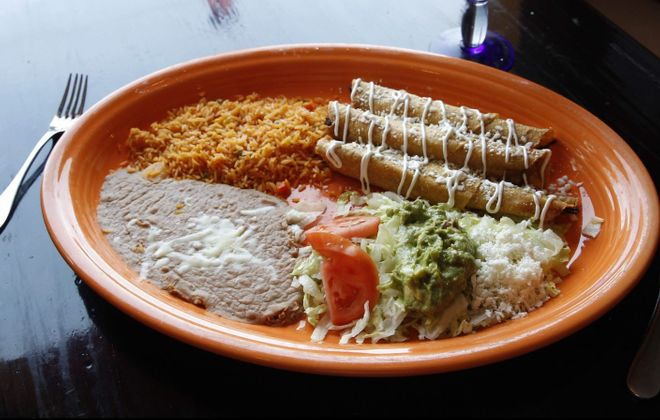 Three shredded chicken or beef flautas, topped with sour cream and fresh queso served with Mexican rice, beans and guacamole salad. (Sharon Cantillon/Buffalo News)